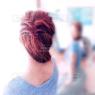 髪を束ね鏡を見る女性の写真・画像素材[4744910]