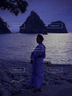 夜の砂浜に立つ浴衣の女性の写真・画像素材[4754212]