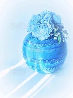 丸い花瓶に活けた水色の花と実の写真・画像素材[4838637]