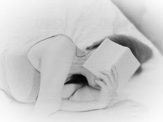 本を読みながら寝てしまった女性の写真・画像素材[4860317]