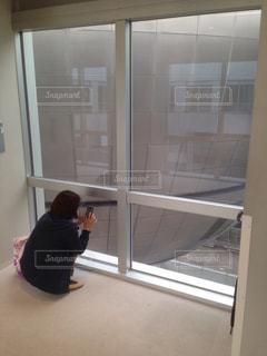 窓の前にしゃがみ込む人の写真・画像素材[2290510]