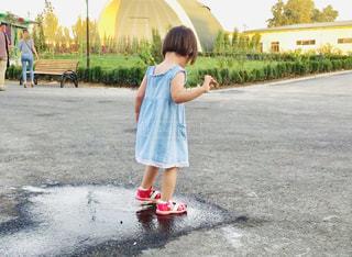 水たまりの上に立っている小さな女の子の写真・画像素材[2262631]
