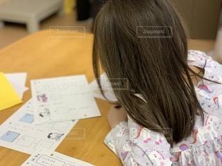 後ろ姿,子供,女の子,テーブル,書類,デスク,宿題,プリント,紙,データ,平仮名,用紙