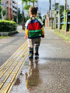 レイブーツを履いた幼児が水溜りを歩く 水溜りに姿が映る 雨が止んですこし晴れてきた時の写真・画像素材[4562221]