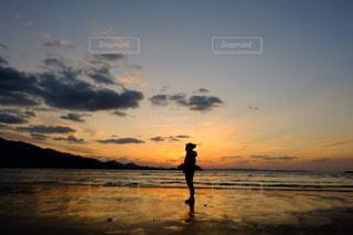 夕焼けを背景にビーチに立つ男の写真・画像素材[2333871]