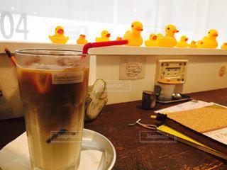 テーブルの上のコーヒーの隣にオレンジジュースを一杯の写真・画像素材[2264490]