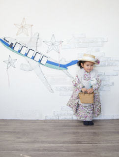 飛行機が描かれている壁の前で着物を着て立っている女の子の写真・画像素材[2272449]