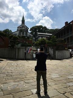 レンガ造りの建物の前に立っている男の写真・画像素材[2278612]