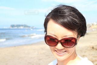サングラスをかけて浜辺で微笑んでいる女性の写真・画像素材[2278204]