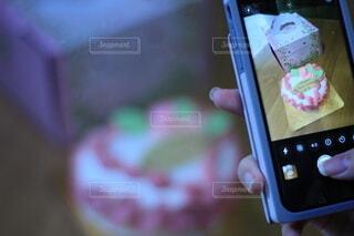 携帯電話を持ちケーキの写真を撮る。の写真・画像素材[4811304]