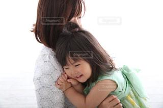 赤ん坊を抱いている小さな女の子の写真・画像素材[2365023]