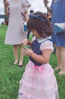 ピンクのドレスを着た小さな女の子の写真・画像素材[2377573]