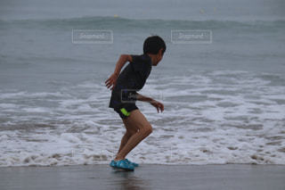 浜辺の上で波に乗っている男の写真・画像素材[2337330]