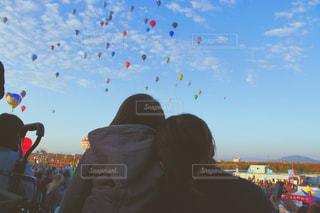 カラフルな凧が空を飛んでいるのを見ている人々のグループの写真・画像素材[2363895]