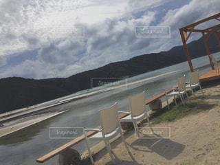 砂浜の上に座っている木製のベンチの列の写真・画像素材[2347847]