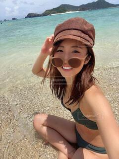 水の体の近くのビーチに座っている女性の写真・画像素材[3671360]