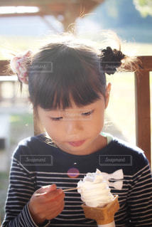 牧場でソフトクリームを食べる女の子の写真・画像素材[2397482]