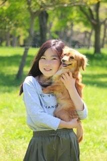 緑の中の少女と犬の写真・画像素材[2702639]