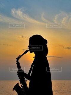 夕焼けとサックスを吹く少女の写真・画像素材[4820825]