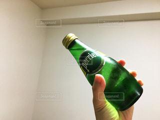 緑の瓶を持っている手の写真・画像素材[909405]