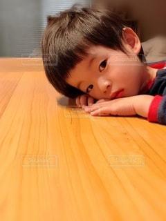 横たわってカメラを見ている小さな男の子の写真・画像素材[2736324]