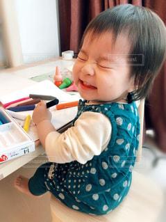 テーブルの上に座っている小さな子供の写真・画像素材[3174012]