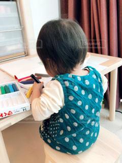 テーブルに座っている小さな女の子の写真・画像素材[3221561]