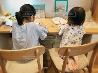 テーブルに座っている小さな女の子の写真・画像素材[3408258]