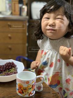 テーブルに座っている小さな女の子の写真・画像素材[2327602]