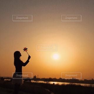 夕陽に照らされる女性のシルエットの写真・画像素材[971163]