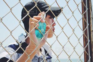 フェンスの横に立っている人の写真・画像素材[1185217]