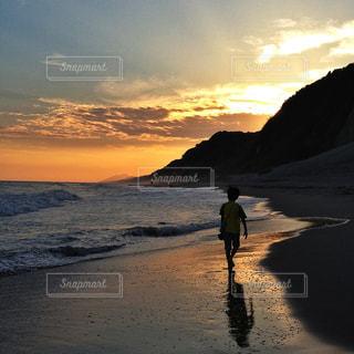 自然,海,空,夕日,ビーチ,砂浜,夕暮れ,波打ち際,波,シルエット,少年,野外
