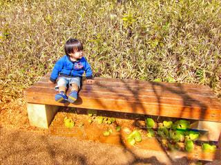 ベンチに座っている小さな男の子の写真・画像素材[2415406]