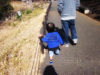 草の上に立っている小さな男の子の写真・画像素材[2415411]