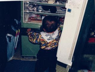 冷蔵庫の前に立っている人の写真・画像素材[2432428]