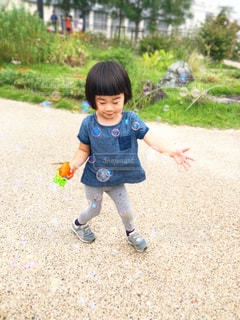 草の上に立っている小さな男の子の写真・画像素材[2414928]