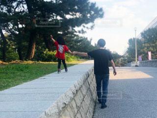 道路の脇を手を繋いで歩く親子の写真・画像素材[2548340]