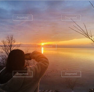 夕陽を撮影する娘の後ろ姿の写真・画像素材[3901220]