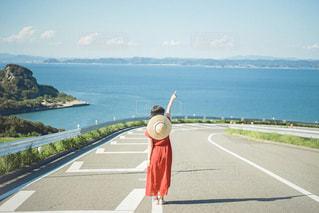 道路の隣の水域の隣に立っている人の写真・画像素材[2794988]