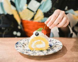 テーブルの上にケーキを置いたまな板の上に座っている人の写真・画像素材[2809075]