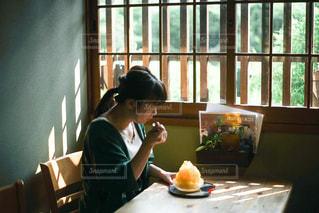 窓の前のテーブルに座っている人の写真・画像素材[2873859]
