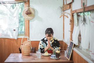 テーブルの上に座っている人の写真・画像素材[2873865]