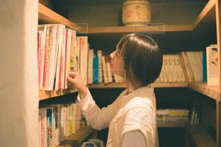 本棚の前に立っている人の写真・画像素材[2892962]