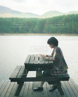 水域の隣のベンチに座っている人の写真・画像素材[2892965]