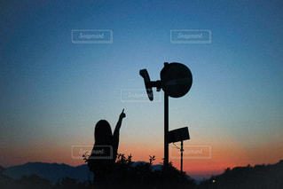 背景に夕日がある人の写真・画像素材[2938354]