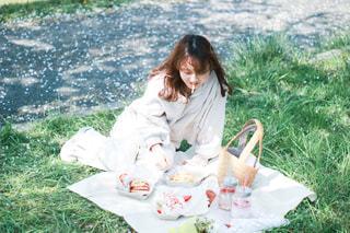 草の中に座っている小さな女の子の写真・画像素材[3054709]