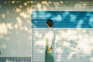 窓の前に立っている人の写真・画像素材[3104280]