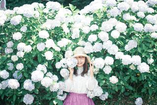 花の庭の前に立っている女性の写真・画像素材[3141913]