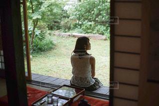 窓の前のテーブルに座っている人の写真・画像素材[3170984]
