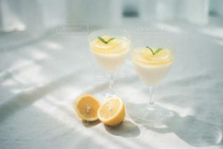コップ一杯の水の隣にオレンジジュースを1杯入れたの写真・画像素材[3195798]